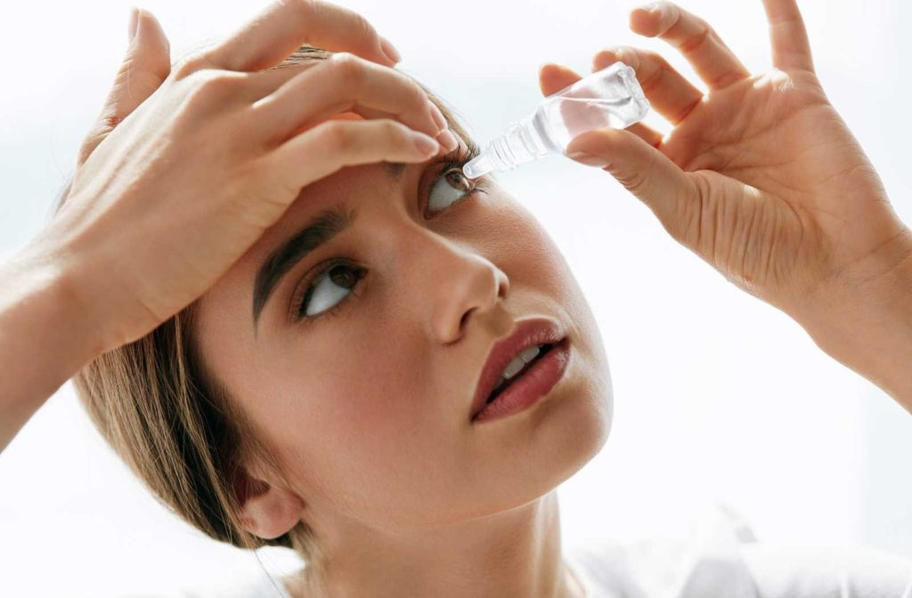 young woman carefully applying eye drops on white background