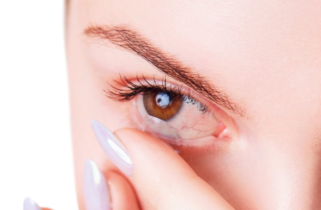 Woman with bloodshot dry eye inserting contact lens