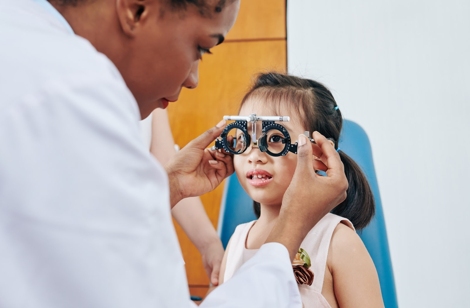 Young girl being fit for eyeglasses by an optician