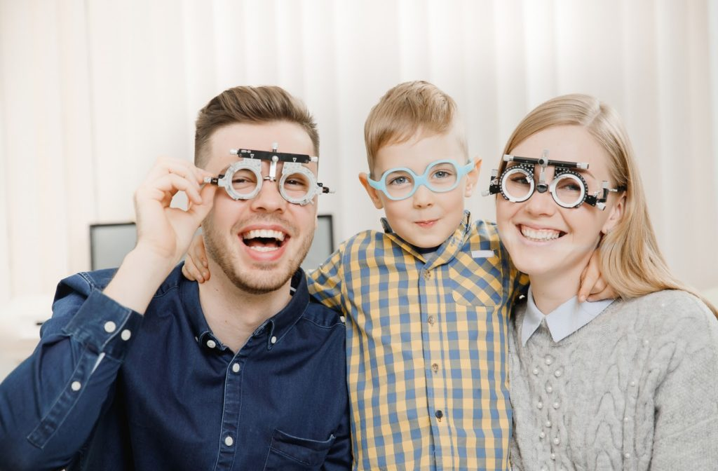 Cheerful family at the eyes doctor ready to have their eye exams.