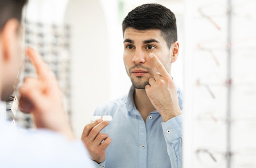 Man at the optometrist office putting on pair of contact lens in the mirror.