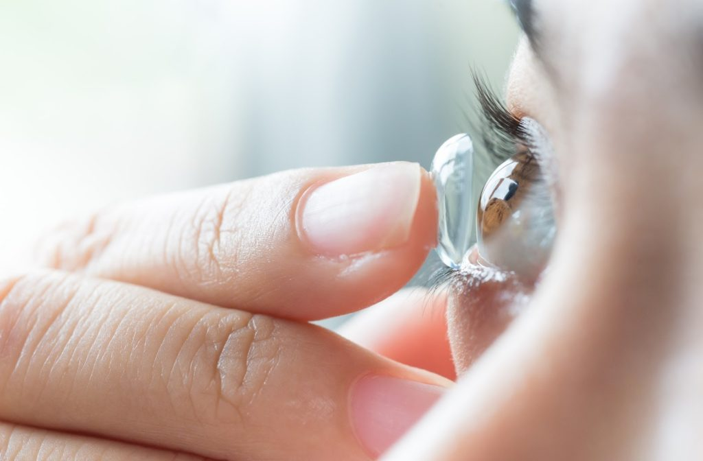 Woman putting contact lens in her eyes.