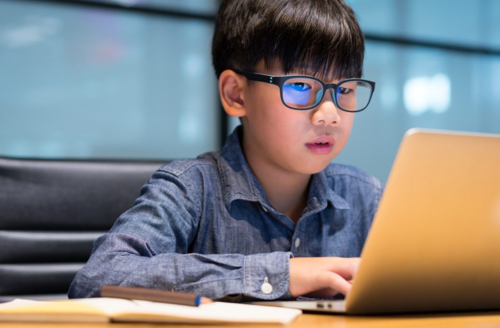 Young boy wearing blue light glasses while using laptop to finish homework