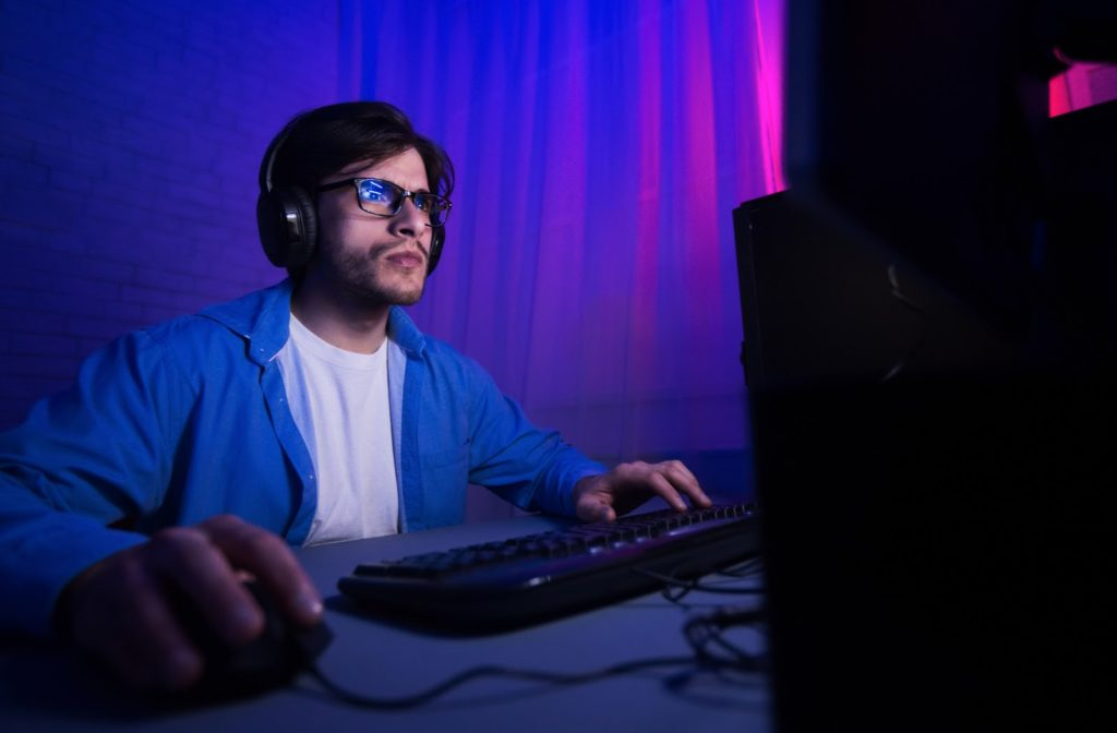 Young man wearing blue light glasses while playing video games on computer at night