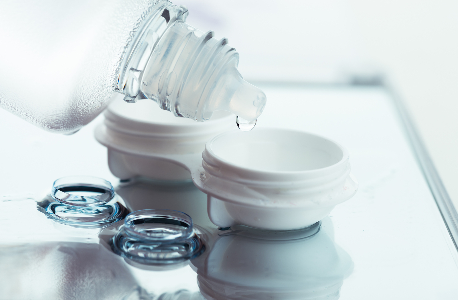 Contact lens case being filled up with solution with lenses on side of table